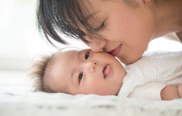 赤ちゃんの頬にキスする母親